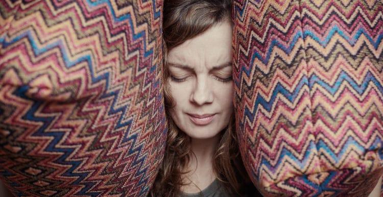 Migräne_Frau mit Kopf zwischen Kissen
